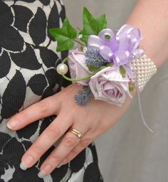 A stunning artificial Wedding wrist corsage, with a slight   cottage garden feel. Two lilac Chloe roses, two purple  lavender spray's and loop of beargrass with a large bead.  Spray of ivy, light catching crystals and lilac mixed sheer   organza bow with trails.  This beautiful wrist corsage is attached to an elasticated  Ivory pearl wristband, easy to pop over your hand on to your   wrist.    Measurements  Width:- 4 inches  Length:- 4.5 inches