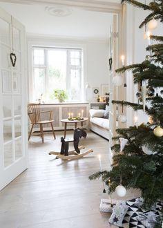 ET MAGISK JULEHJEM MED HJEMMELAVET PYNT: Hos familien Lindholm er julen forvandlet til en magisk tid med overkommeligt juleklip, hjemmebag og masser af hyggestunder. [...] I forgrunden står familiens ædelgran og blærer sig med sin fine pynt i hvide nuancer. De franske døre åbner op til familiens hyggelige stue med en sofa fra Domus Interieur, en stol fra en loppemarkedstur og et sofabord, som familien har fået i gave. Gyngeelgen er fra Ikea. Den var oprindelig rød, men fik en omgang brun…