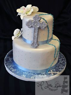 This communion or confirmation cake design is a new addition to our cake gallery. The 2 tiered fondant iced cake has a pearl finished and is adorned with a cross and rosary beads. As a topper we added hand made sugar orchids. The cross is made of modeling chocolate with a silver finish.