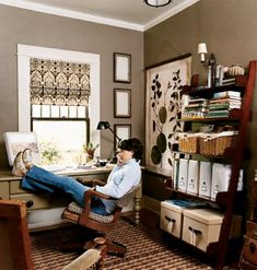 A desk is positioned in front of the window in this home office, while ladder shelving with decorative storage containers are organized on the opposite wall. Chocolate brown walls and black, brown and cream window treatment completes the look of this workspace.