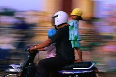 Dad takes the kids, perilously, through Phnom Penh on the back of the motorbike.