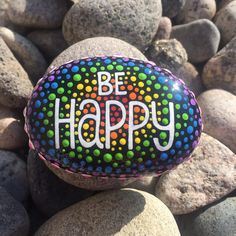 This is a hand painted rock with the words Be Happy painted in white. The background is filled with red, orange, yellow, green, blue, purple and pink dots faded together. The rock is sealed with a clear shiny finish. However it is best for indoor use or on a covered porch due to