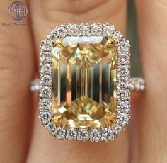 This gorgeous fancy yellow emerald cut diamond engagement ring is encompassed in a halo of micropave set round diamonds. View our website to see more emerald designs. by doreen. Emerald Cut Diamond Engagement Ring, Emerald Cut Rings, Engagement Ring Cuts, Emerald Cut Diamonds, Colored Diamonds, Round Diamonds, Diamond Cuts, Yellow Diamonds, Pink Sapphire