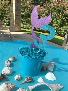 Welcome to Sweetheart Party Shop! This listing is a large purple glitter mermaid tail and aqua glitter age centerpiece stick. Mermaid tail cutout is 9 inches tall and age cutout is 5 inches tall, both are attached to 8 inch sticks. **Listing DOES NOT include bucket, crinkled