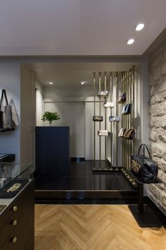 MASHA KEJA   Archipelles PARIS Agency.   Rennovation of a shop. Boutique. Stone wall. Gold metal. Costum made display island. Costom made display shelves and cabinets. Costom made counter and cashier desk.