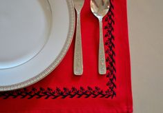 A set of 4 cotton placemats in true red with jet black embroidery all long the placemat. These mats are perfect for the holidays and more. The embroidery in black adds a touch of elegance to the table setting.