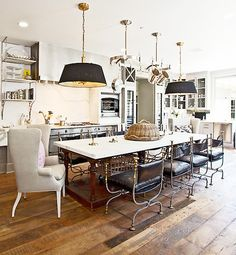 Actress Gwyneth Paltrow transforms her kitchen into a real eat-in, entertain-in space by warming it up with typical living room accents: fabric pendant lamps, upholstered armchairs and side benches for extra seating.