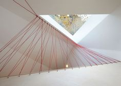 Webs of red parachute cables take the place of traditional balustrades between the two levels of this office