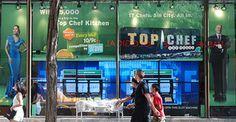 People walking by a digital shop front window