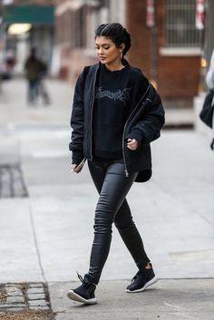 Wheretoget - Kylie Jenner wearing black leather pants, black sneakers, a black printed sweatshirt, and a black jacket