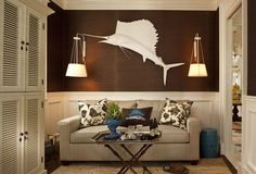 Taylor-taylor: Matte white paint helps a taxidermy sailfish to become a focal point on a wall covered in chocolate-colored grass cloth. The sconces were sourced at Urban Electric.
