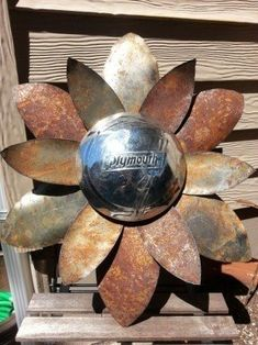 Rusted hammered metal flower wall hanger with Plymouth hubcap yard
