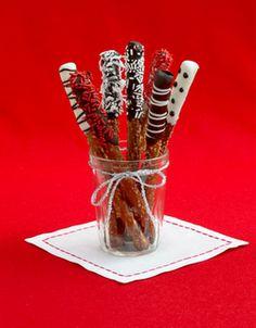 Os tradicionais biscoitinhos doces em forma de palito ganham coberturas de chocolate preto e branco enfeitados com granulhados