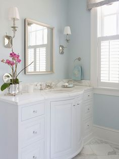 Dream Bath in Blue: Separate Spaces A pair of long vanities flanks each side of the entrance from the master bedroom. Separate vanities have made it easier for the two homeowners to share a bath without bumping in to each other while they get ready in the morning. Curved fronts give the vanities a graceful appearance that complements the elegant lines featured on the bathtub.