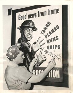 "1943- Mrs. Douglas, an ordnance worker and cartridge inspector, adds the word ""ammunition"" to a war production poster at the U.S. Cartridge Company plant in St. Louis. She has five sons in the US Navy."