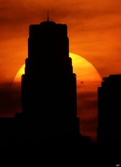 Venus is silhouetted as it crosses in front of the sun as it sets behind the Kansas City, Mo., skyline, Tuesday, June 5, 2012.