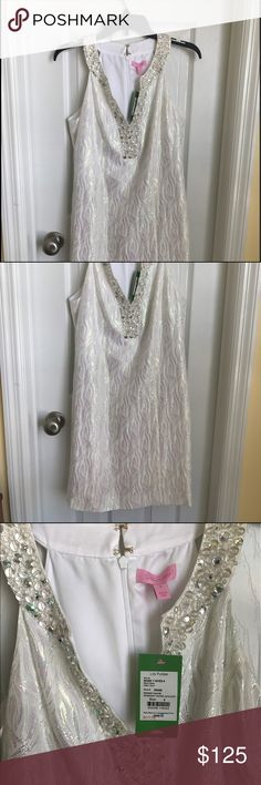 Lily Pulitzer dress This is a beautiful shimmery dress with a beaded v- neck. Prefect dress for the summer wedding or out on the town. It hits above the knees. It has never been worn! Lilly Pulitzer Dresses Mini