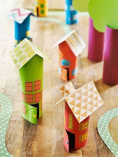 Transform cardboard tubes into cute cottages in just a few simple steps.   Paint the tube and let it dry. Make two angled cuts into one end of the tube to form a point. Fold a 3- by 3 1/2-inch piece of scrapbook paper in half, then set it on the pointed end as a roof. Use tacky glue to secure it. Make two cuts to create a rectangular door, as shown. Glue on a bead for a doorknob. Draw windows onto colored paper, cut them out, and attach them to the cottage using a glue stick. For...
