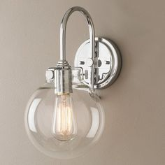 """Retro and modern combine to bring clear light to your home or bath.  Available in polished chrome, antique nickel or bronze the clear round globe complements the detail of the metal.  (1) 100 watts max medium base.(13.5""""Hx7""""Wx9.3""""D)4.75"""" Backplate"""