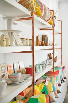 White and copper shelving.  Cute.