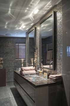 Masculine bathroom. Love the glass sinks... Tile behind the mirror!!