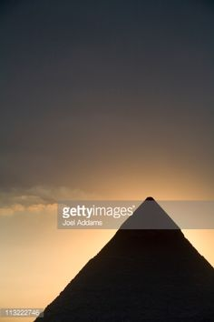 The Pyramids at Giza silhouetted against a setting sun in Giza, Egypt.