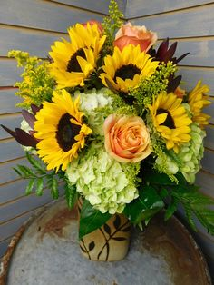 An autumn designed keepsake vase is filler with gorgeous blooms of sunflowers, roses, hydrangeas, solidago and even sunset safari. It's a beautiful combination of flowers that bring autumn into the home of your recipient.