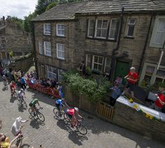 The seven leading riders ride up Main Street as stage two of the Tour de France passes through Haworth, Yorkshire. PRESS ASSOCIATION Photo. See PA story CYCLING Tour. Picture date: Sunday July 6, 2014. Photo credit should read: Tim Goode/PA Wire