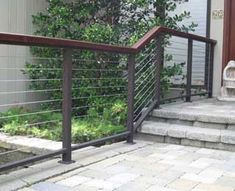 This Modern Cable Railing is fabricated with a 1 by 2 aluminum top and bottom bar bar with IPE wood top molding, 2 square aluminum posts and 3/16 stainless steel cables. The posts were mounted with 4 square plates and secured to the paver blocks with fasteners. The railing flanks the main entrance to the clients home. CR-14