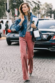Pink corduroy pants offer a fun texture to a simple outfit of a denim jacket & gray tee.