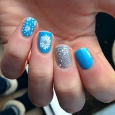 Cute blue floral nail art design. With blue as the base color, the flower details are painted with white polish. Silver glitter is also added to the design as accent.