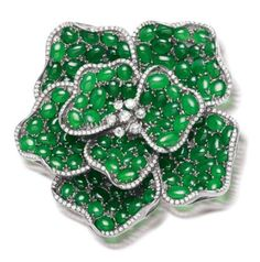 A jadeite and diamond brooch The petals set throughout with intense green jadeite cabochons of good translucency, highlighted by a brilliant-cut diamond border, and rose-cut diamond stamen, diamonds approximately 1.50 carats total, length 5.8cm.
