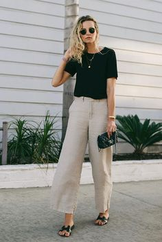 25 Ultra-Fresh Summer Looks To Wear To Work: Fashion blogger 'Anouk Yve' wearing a black t-shirt, beige linen trousers, black sandals, round aviator sunglasses and a black quilted bag. Work outfits, wear to work, summer work outfits, office looks, office wear, summer outfits, street style, fashion trends 2018, summer style, office style, #weartowork #officestyle #streetstyle #summerstyle #fashion2018 #fashiontrends2018 #9to5chic #bossbabe #ss18 Linen Trousers, Trousers Women, Work Trousers, Black Linen Pants, Skandinavian Fashion, Culotte Style, Fashion 2018, Fashion Outfits, Style Fashion