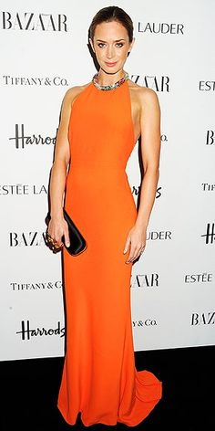 EMILY BLUNT  Radiant in a backless tangerine halter gown (that editors here are drooling over), plus a black clutch and cocktail rings, the actress attends the Harper's Bazaar Women of the Year awards in London.