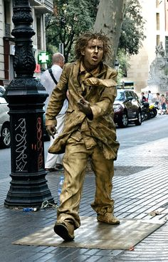 HUMAN STATUES are a huge attraction on Las Ramblas, standing  absolutely lifeless for hours in difficult poses like this. Las Ramblas, in Barcelona, Spain, is a large pedestrian street lined with restaurants, cafes, souvenir shops, and flower kiosks, and bustling with tourists, locals, hustlers and performing artists of all kinds.  October 2011