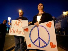 Ian Anderson, right, and Rob Servis, of Tucson, stand outside the offices of U.S. Rep. Gabrielle Giffords, D-Ariz., during a candlelight vigil for Giffords Saturday, Jan. 8, 2011 in Tucson, Ariz. Giffords was shot in the head earlier in the day during a speech at a local supermarket. (AP Photo/Matt York)