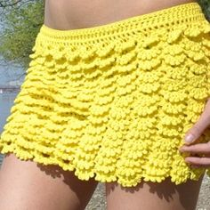 This yellow mini skirt combines crocheted lace and bright color to create a fabulous layered design