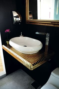 The black tiles make a good backdrop for the gold-mirrored frame and mosaic tiles.