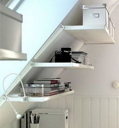 Since most attics have steep walls, they're not always the most convenient storage spots — unless you take advantage of open shelving as was done in this room. Suddenly an unlikely wall becomes a convenient spot for a desk. Store supplies on sloped shelves and snuggle the desk up underneath. Click through for more on this and other attic storage solutions.