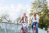 Photo: Senioren Paar mit Fahrrädern auf Brücke