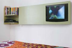 TV no quarto. Estreita, a suíte do casal, de 9 m², não tinha espaço para uma estante tradicional. Como solução, a arquiteta Clarissa Guimarães desenhou o módulo laminado, de 26 cm de profundidade (suficiente para comportar TV e DVD e camuflar os fios), instalado à frente da cama.