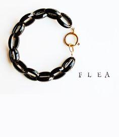 Onyx black vintage faceted plastic link bracelet with oversize brass clasp.
