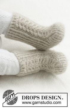Knitted socks with cables and rib for baby. Size 1 month - 4 years Piece is knitted in DROPS Puna.
