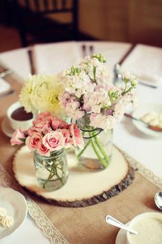 Natural centerpiece in pastels with mason jars and wood slab accents