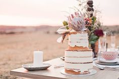 2 tier naked wedding cake wonder with feathers & the grand king protea. Bohemian theme, country weddings