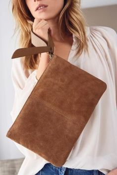 A staple hue for every girl's wardrobe! Add a pop of tan to your outfit this spring with our leather wristlet clutch bag!