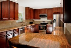 cherry cabinets, high glass wood like countertops, stainless steel appliances, kitchen remodel... by the BEST custom home builder / remodeler in central Florida | www.allinconstruction.com