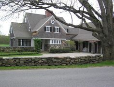 grey, white trim, black shutters, stone, and shingles all brought together for a wonderful warm look for this home