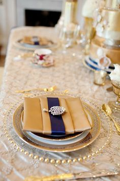 Royal wedding inspired by Courtenay Lambert Florals. Gold satin napkin on place setting.