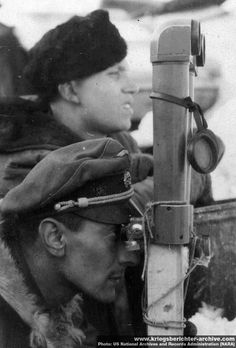 "Waffen SS officer using scissor field glasses to scope enemy positions, Eastern Front, undated. In the absence of a bipod, the glasses have been secured with string on a wooden stand. The officer is wearing the old-style ""crusher"" cap with non-SS German eagle and braided chin strap. Variety in Waffen SS uniforms and, often, insignia was a permanent characteristic throughout the war."